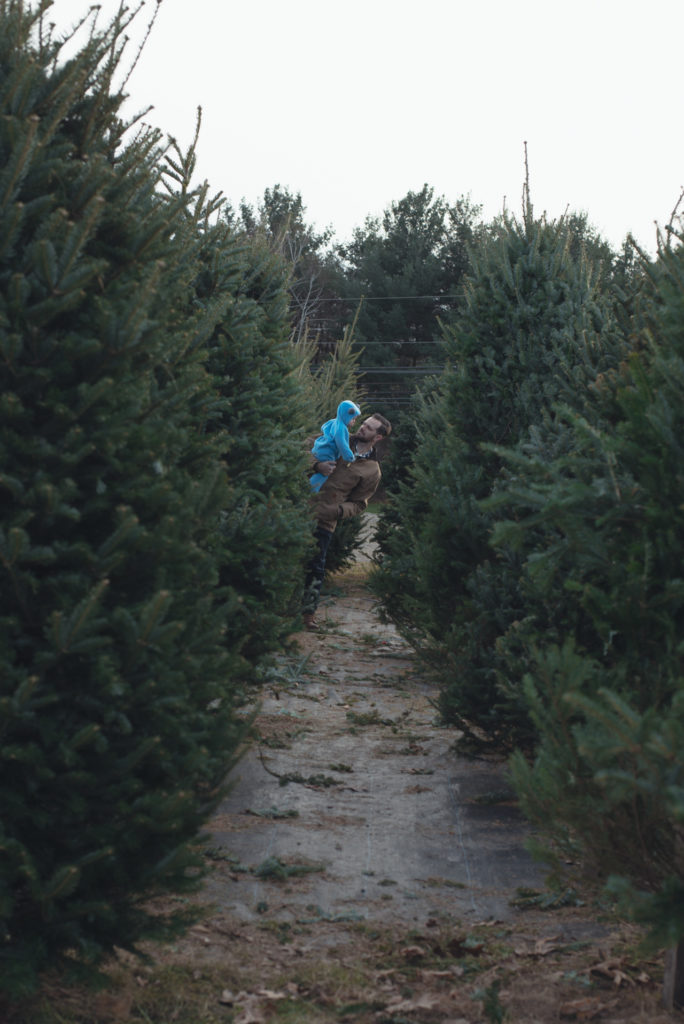 a dad holds his baby boy in an aisle of trees at a farm in connecticut while they pick out their first christmas tree, photographed by jamie bannon photography.