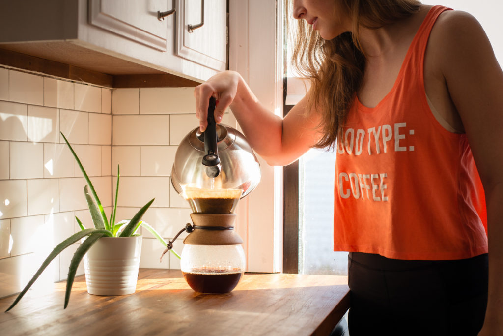 "a woman makes coffee using a chemex pour over coffee maker in a sunlit kitchen wearing a ""blood type: coffee"" shirt from alpha brew coffee, photographed by jamie bannon photography."