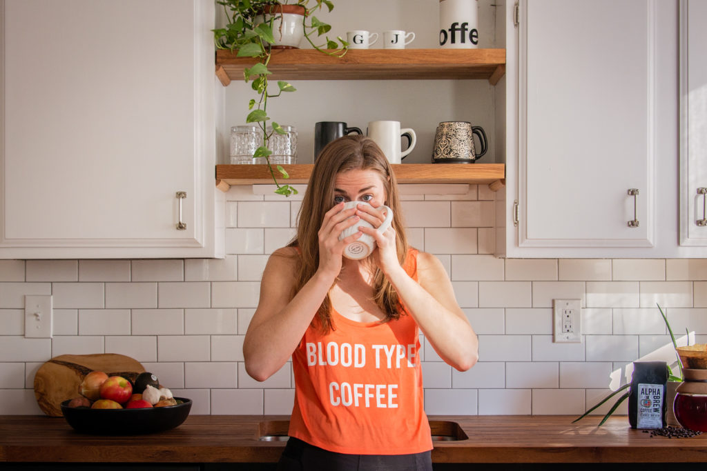 a woman drinks coffee in a sunny kitchen with subway tile and butcher block counters, photographed by jamie bannon photography.