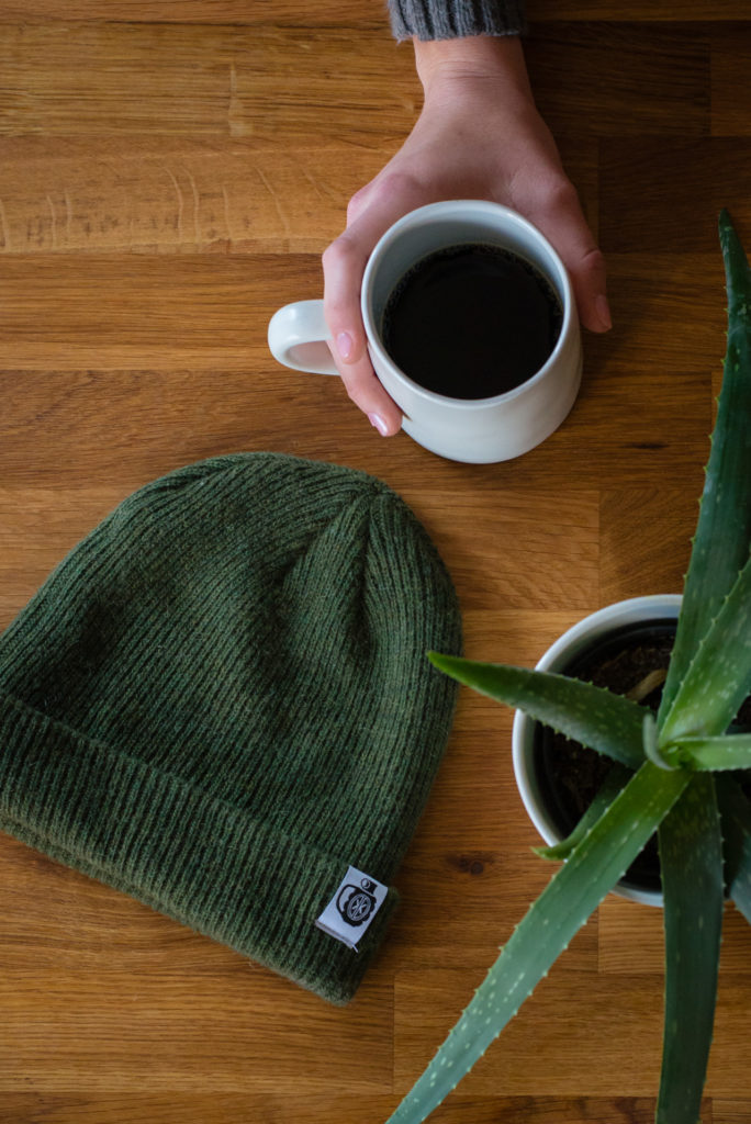 flat lay of a green alpha brew beanie hat, an aloe plant, and a woman holding a cup of black coffee on a butcher block counter, photographed by jamie bannon photography.