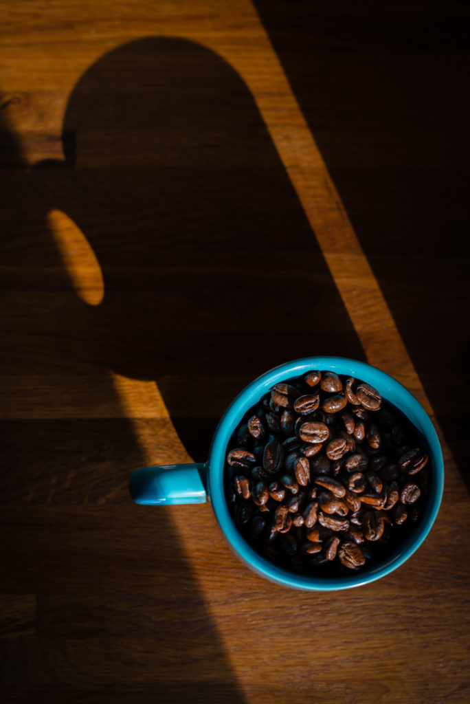 a blue mug holds whole coffee beans on a butcher block countertop with a dramatic shadow cast by sunlight, photographed by jamie bannon photography.