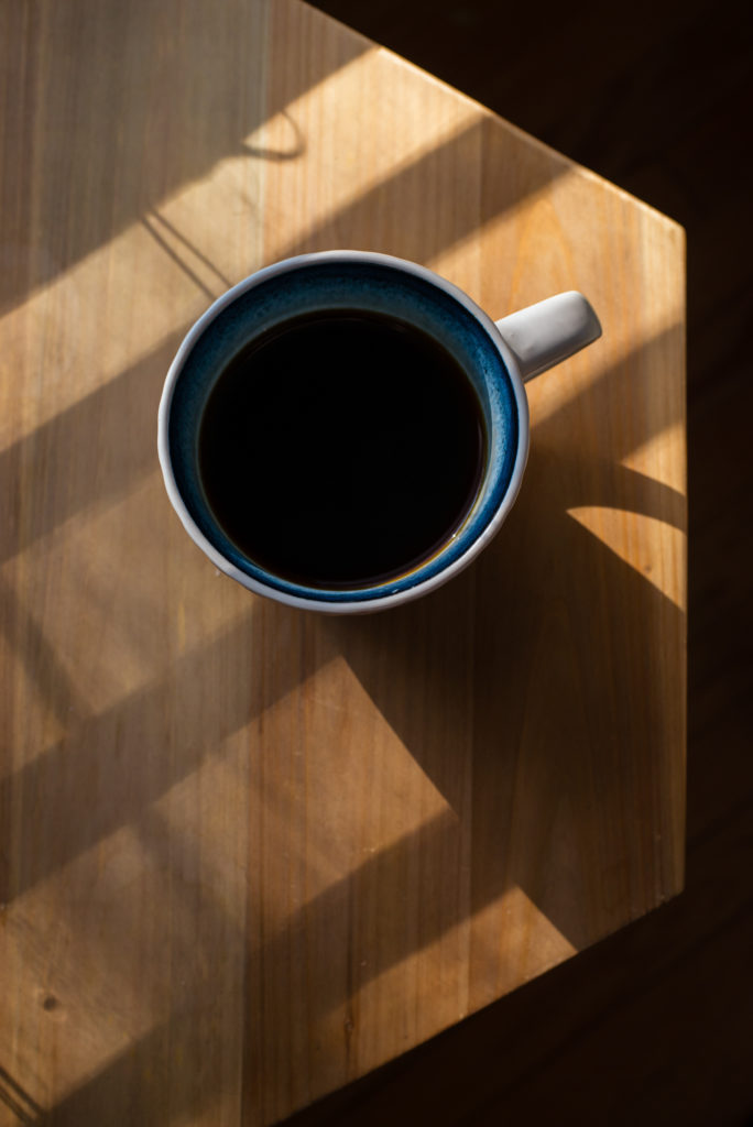 view from above of a cup of black coffee on a geometric wooden side table, photographed by jamie bannon photography.