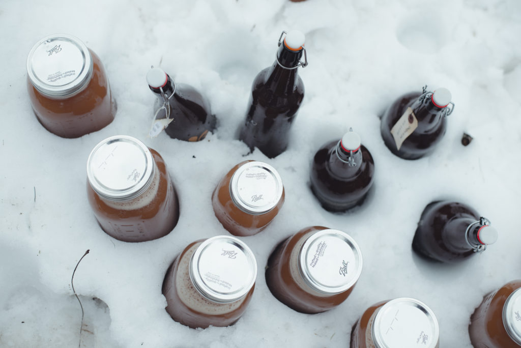 growlers and jars of freshly made apple cider chill in the snow outside on a cold new england winter day in connecticut, photographed by jamie bannon photography.