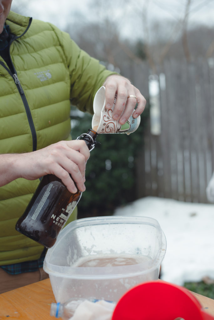 a man pours freshly made apple cider into a growler on a cold new england winter day in connecticut, photographed by jamie bannon photography.