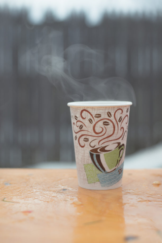 a hot to-go cup of apple cider sits steaming on a table outside in the snow on a cold new england winter day, photographed by jamie bannon photography.