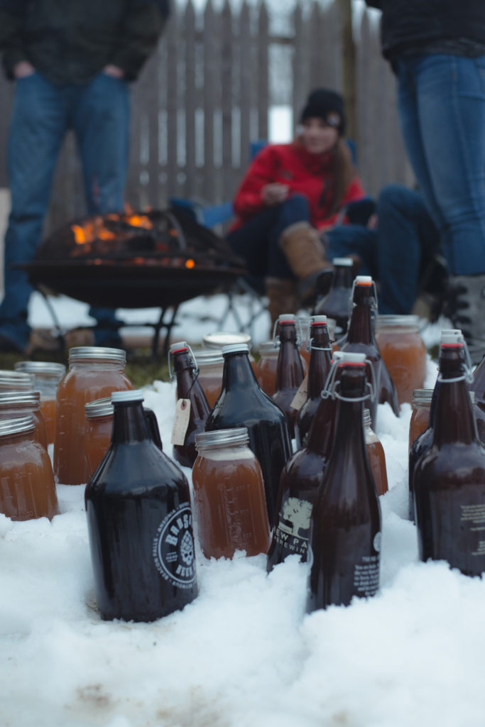 growlers and jars of freshly made apple cider chill in the snow while friends gather around the fire pit in the background on a cold new england winter day, photographed by jamie bannon photography.