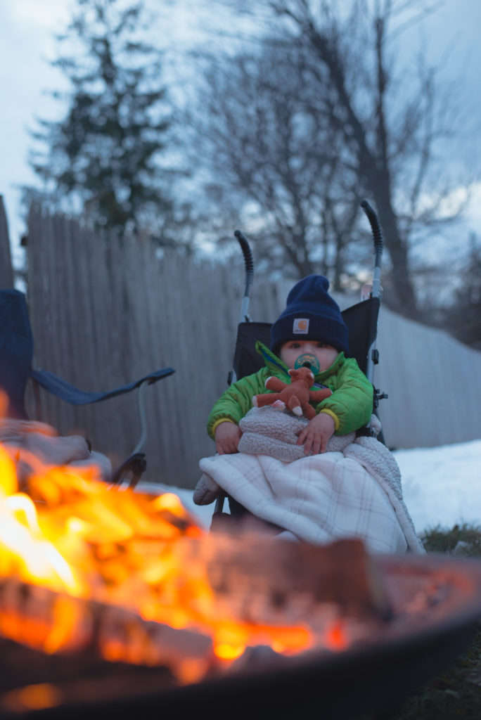 a baby sits bundled up by the fire outdoors on a cold new england winter day, photographed by jamie bannon photography.
