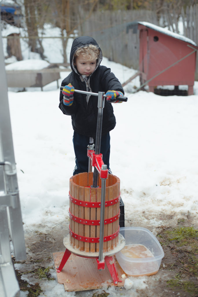 a young boy turns an apple cider press with all his might on a cold new england winter day, photographed by jamie bannon photography.