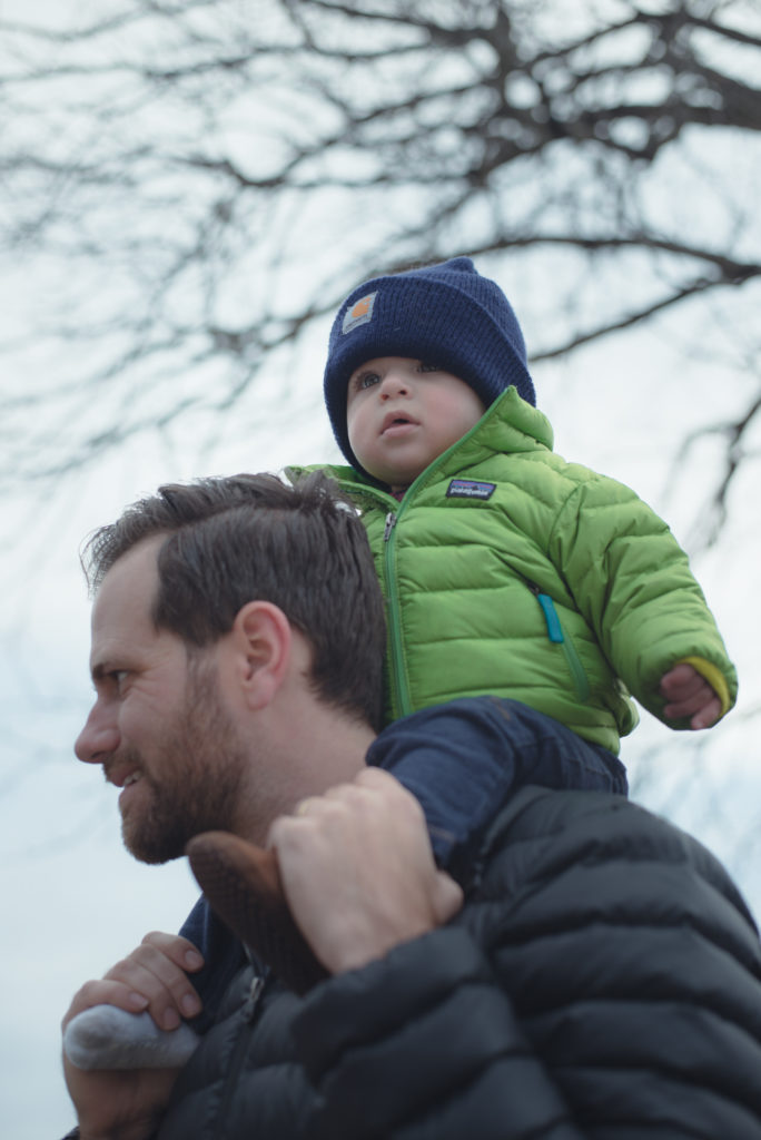 a baby boy rides on his dad's shoulders, bundled up in his patagonia jacket and carhartt hat on a cold new england winter day, photographed by jamie bannon photography.