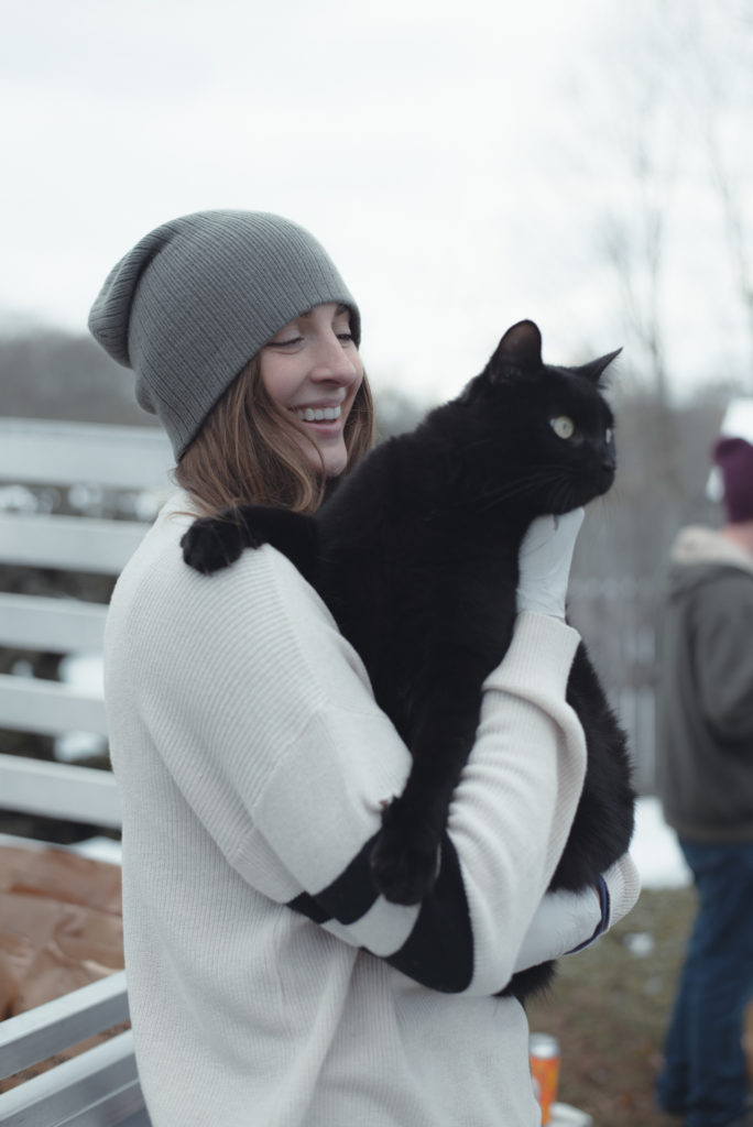 a woman holds and smiles at her black cat on a cold new england winter day in connecticut, photographed by jamie bannon photography.