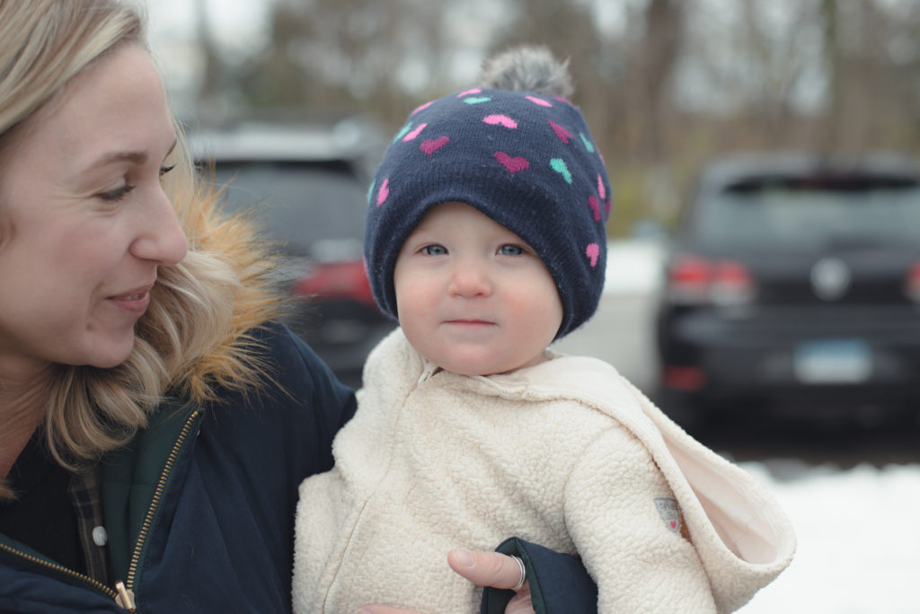 a woman smiles at her baby, bundled up on a cold new england winter day, photographed by jamie bannon photography.