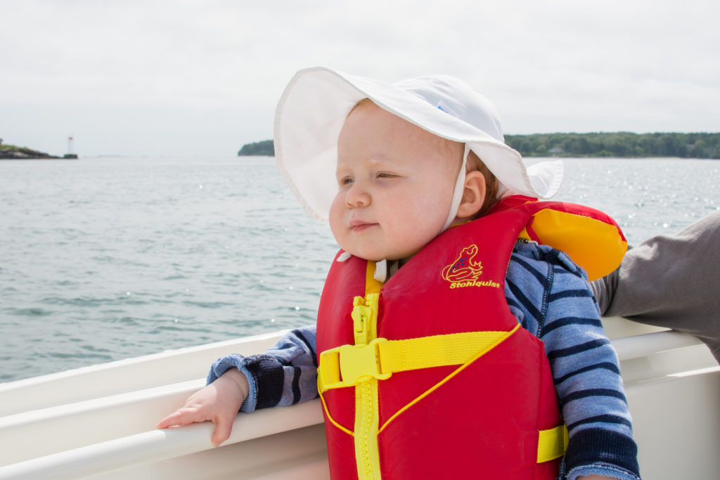 a baby looks off at the sea on a boat off the coast of portland, maine on an overcast summer day, photographed by jamie bannon photography.