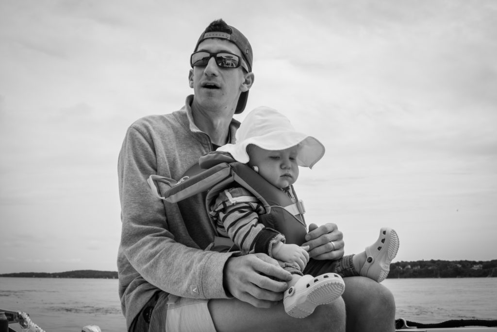 black and white portrait of a dad sitting with his baby on a boat off the coast of portland, maine on an overcast summer day, photographed by jamie bannon photography.