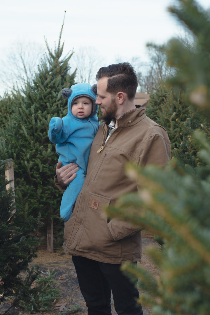 a dad holds his baby boy at a farm in connecticut while they pick out their first christmas tree, photographed by jamie bannon photography.