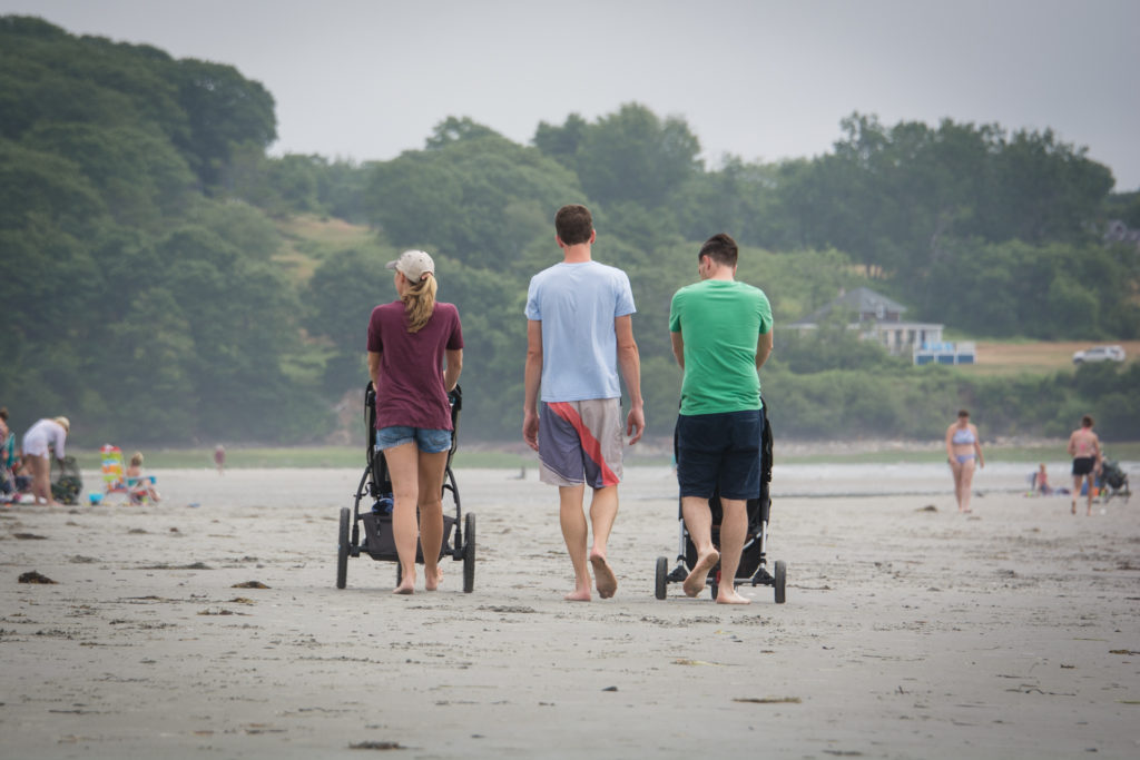 three parents walk with strollers down higgins beach in scarborough maine, photographed by jamie bannon photography.