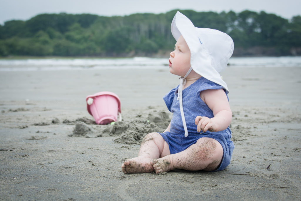 a toddler sits on the sand at higgins beach in scarborough maine, photographed by jamie bannon photography.