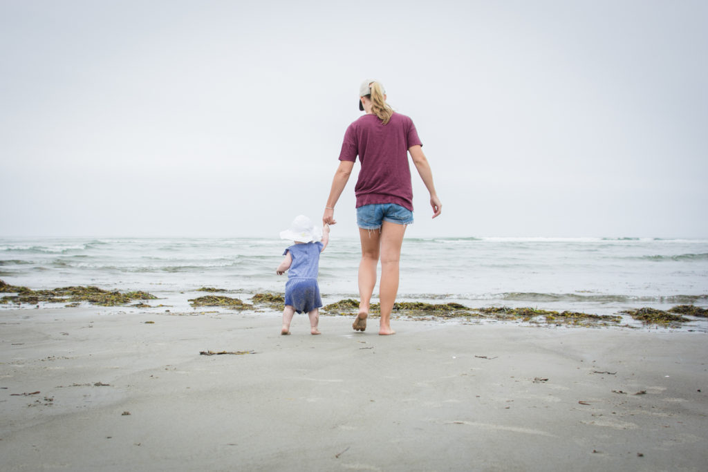 a mom walks toward the water with her toddler at higgins beach in scarborough maine, photographed by jamie bannon photography.