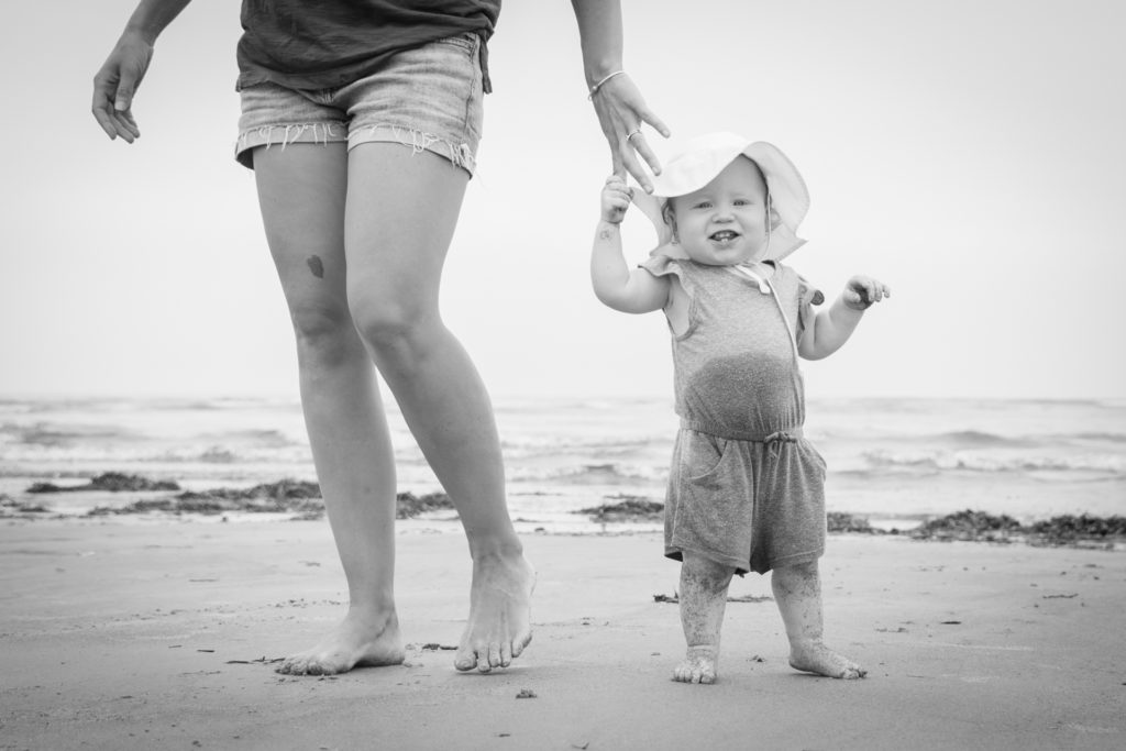black and white portrait of a toddler covered in sand and water holding her mom's hand at higgins beach in scarborough maine, photographed by jamie bannon photography.