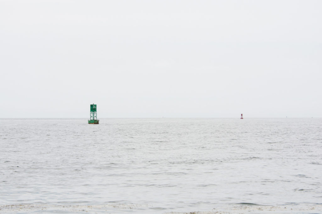 landscape of the ocean off the coast of portland, maine with buoys on an overcast summer day, photographed by jamie bannon photography.