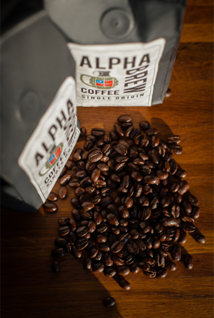 two alpha brew coffee bags with beans spilled on butcher block countertop, photographed by jamie bannon photography.