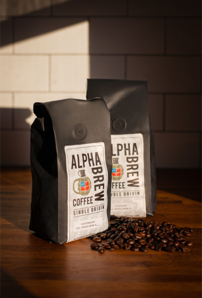 two alpha brew coffee bags with beans spilled on butcher block countertop with sunlight on a subway tile backsplash, photographed by jamie bannon photography.