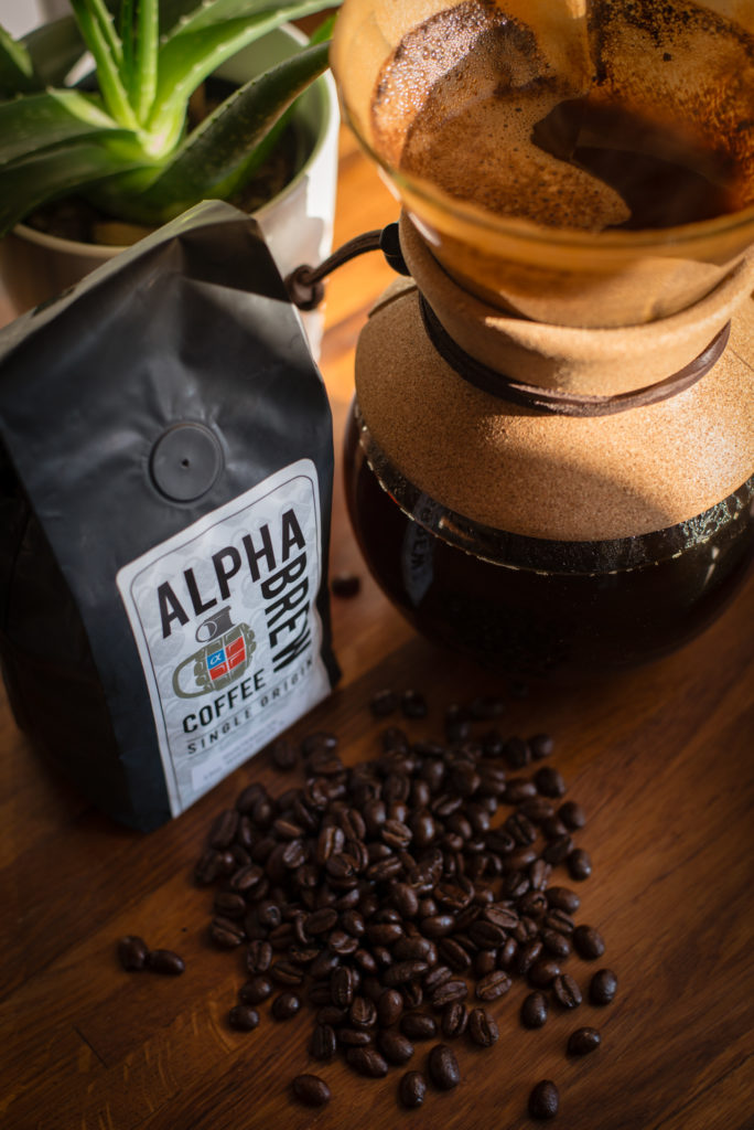 a bag of alpha brew coffee with a pour over coffee maker, aloe plant, and spilled beans on a butcher block countertop , photographed by jamie bannon photography.