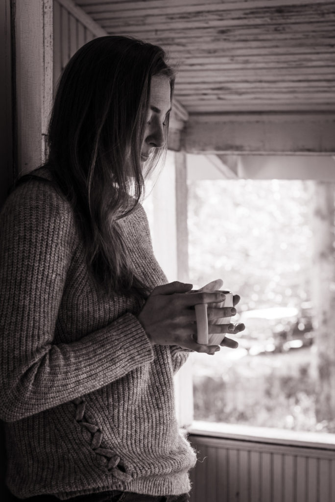 black and white portrait of a woman drinking coffee on her porch, photographed by jamie bannon photography.