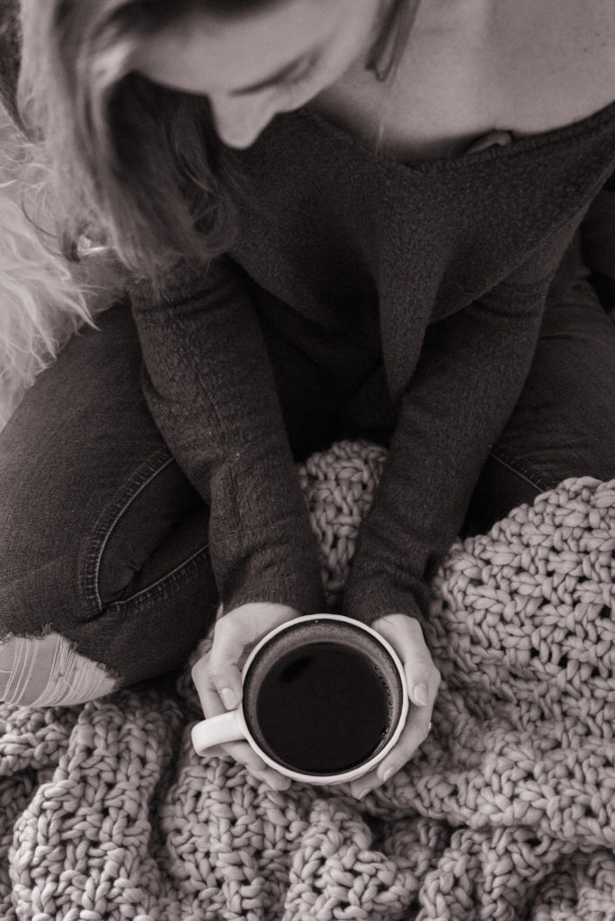 black and white portrait of a woman drinking coffee with a cozy blanket in bed, photographed by jamie bannon photography.