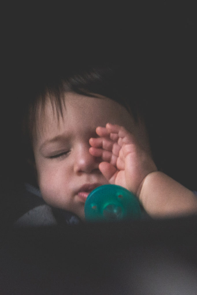 a sleepy baby rubs his eyes in his car seat on a road trip, photographed by jamie bannon photography.