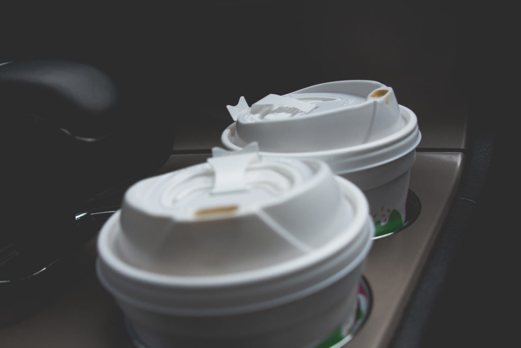 detail of two dunkin donuts coffee cups in the cupholders of a jeep on a road trip, photographed by jamie bannon photography.
