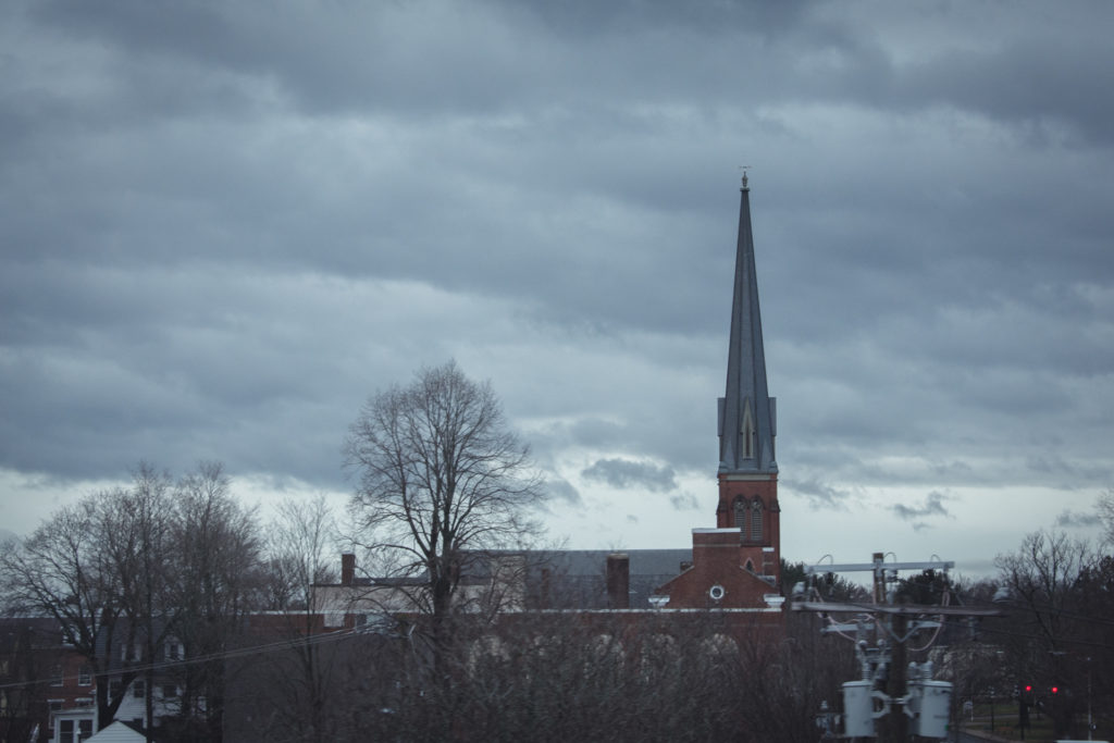 a church steeple against a dark, cloudy, winter sky in connecticut, photographed by jamie bannon photography.