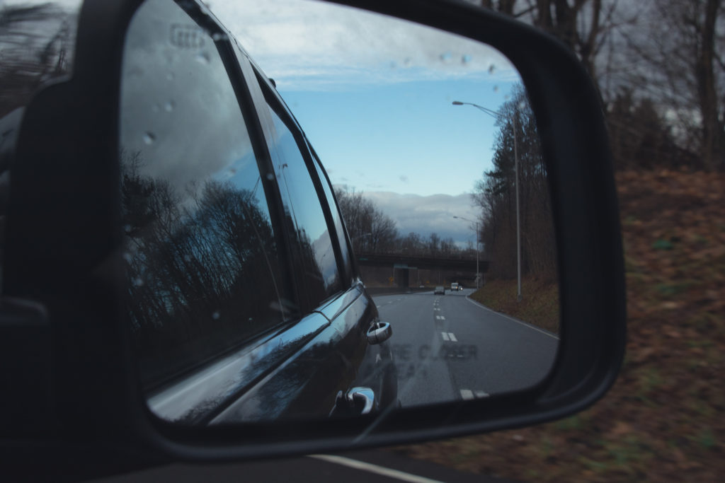 view through a side view mirror of the clouds breaking into blue sky on the highway, photographed by jamie bannon photography.