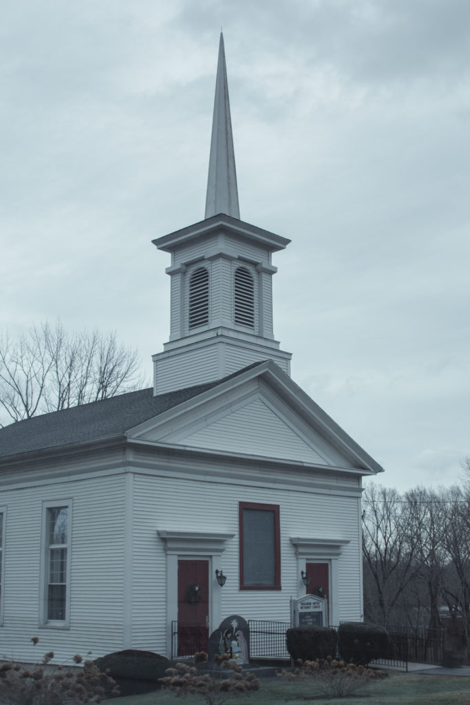 a traditional white church with steeple in new england, photographed by jamie bannon photography.
