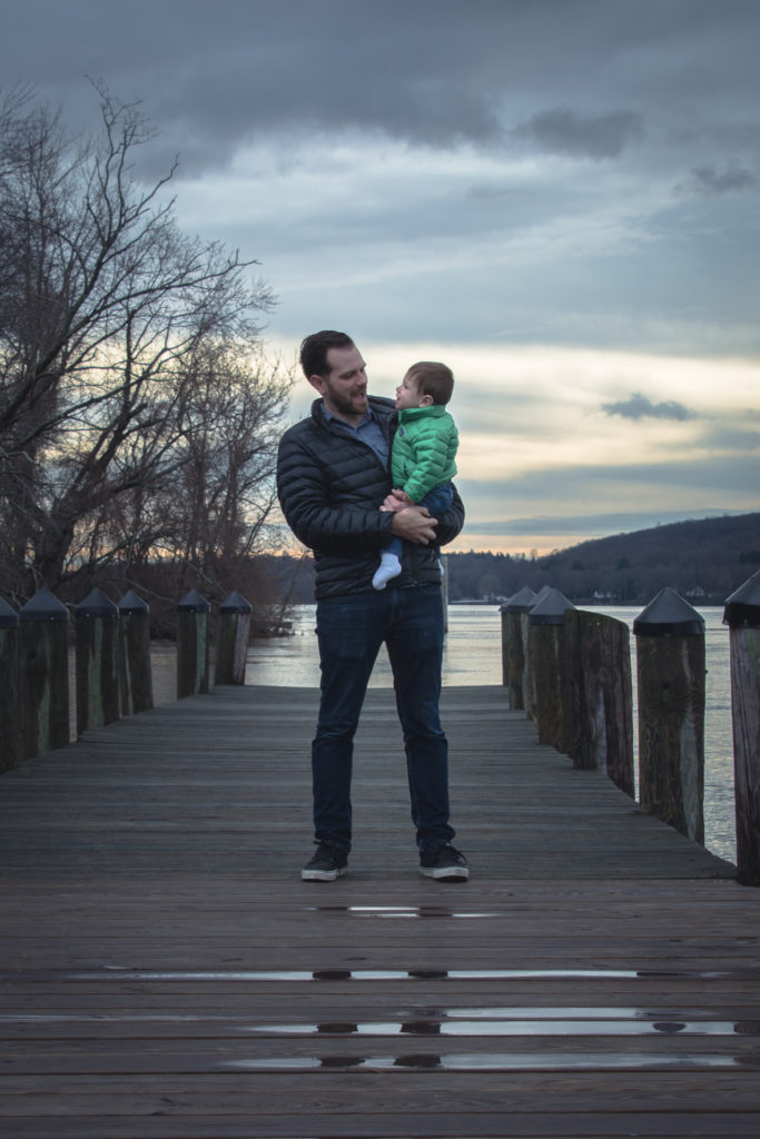 a dad holds his son on the dock at the goodspeed opera house in east haddam, connecticut during the winter, photographed by jamie bannon photography.