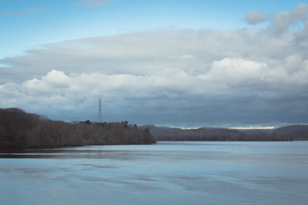 landscape with dramatic clouds over the water in connecticut during the winter, photographed by jamie bannon photography.
