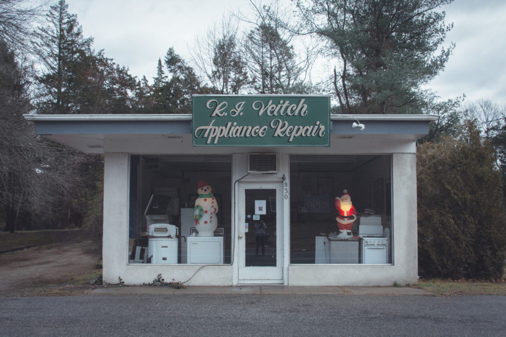 an old appliance repair shop in connecticut with a lit up santa and snowman in the window, photographed by jamie bannon photography.