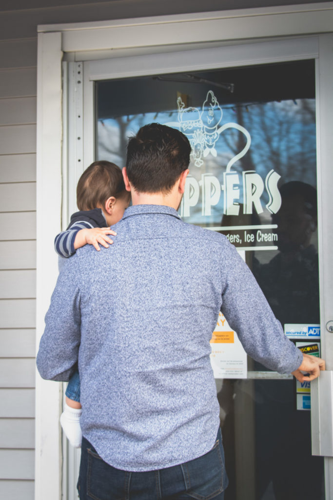 a dad carries his baby into a seafood restaurant in connecticut, photographed by jamie bannon photography.
