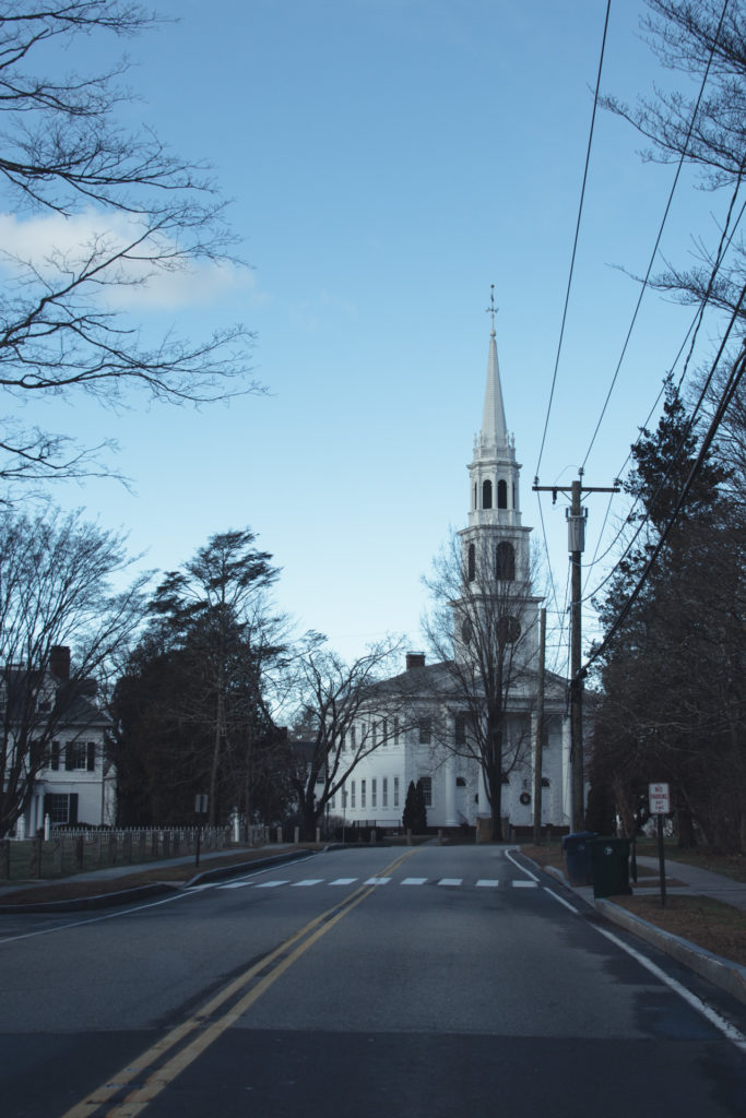 a road leads to a traditional white church with steeple in new england, photographed by jamie bannon photography.