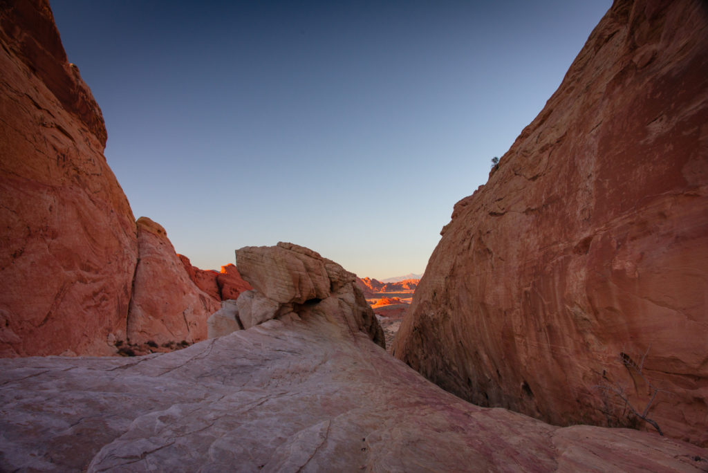 the sun sets over a dramatic landscape of red rocks at valley of fire state park in nevada , photographed by jamie bannon photography.