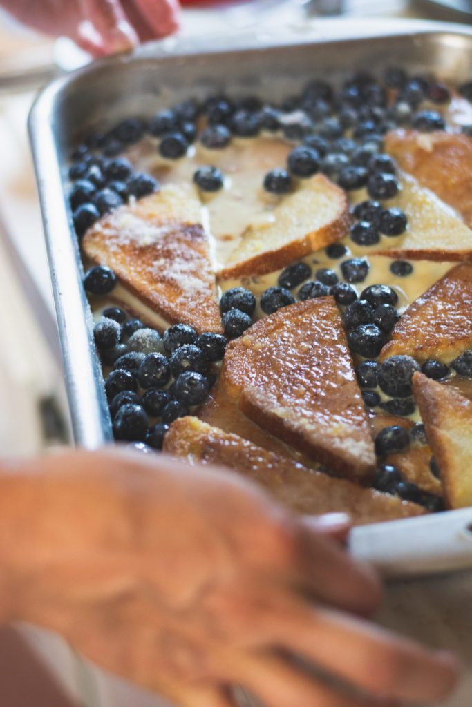 a woman prepares a meal of blueberry french toast, photographed by jamie bannon photography.