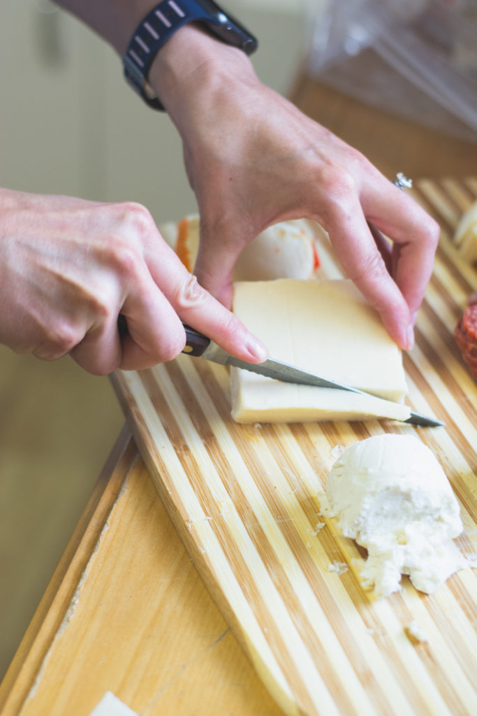 a woman cuts cheese on a cutting board, photographed by jamie bannon photography.