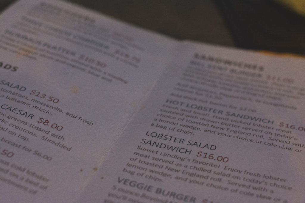 detail of a menu featuring lobster rolls at a restaurant by the beach in niantic, connecticut, photographed by jamie bannon photography.