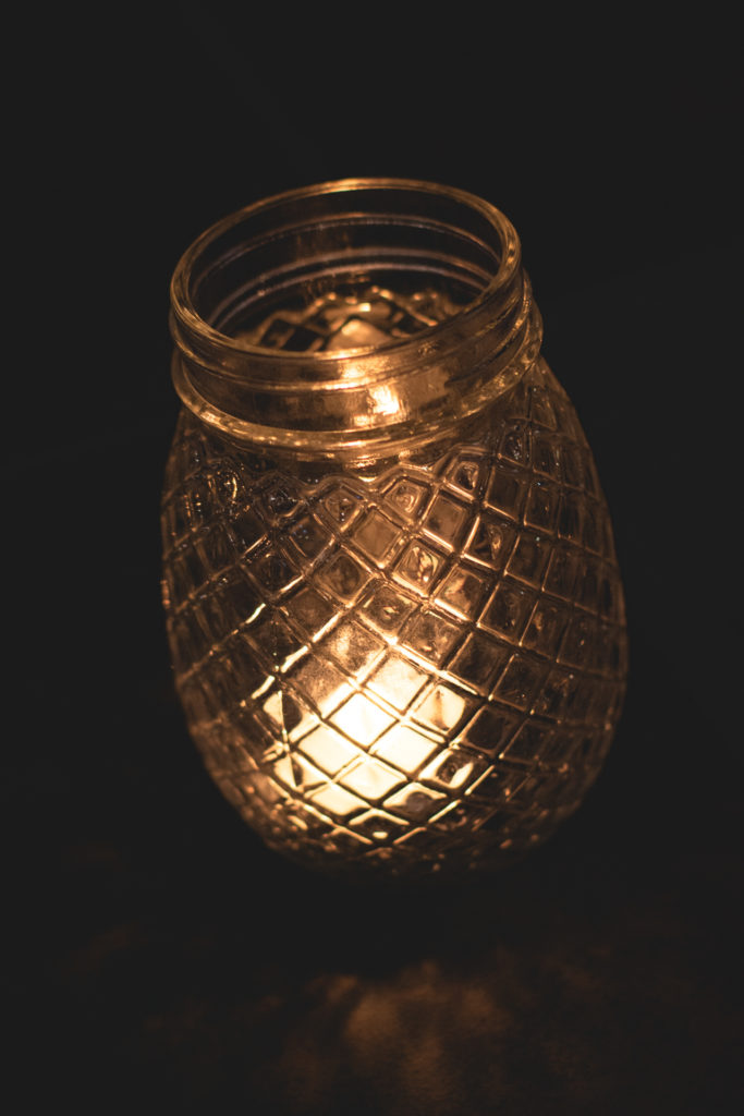 detail of a candle in a jar on a restaurant table in niantic, connecticut, photographed by jamie bannon photography.