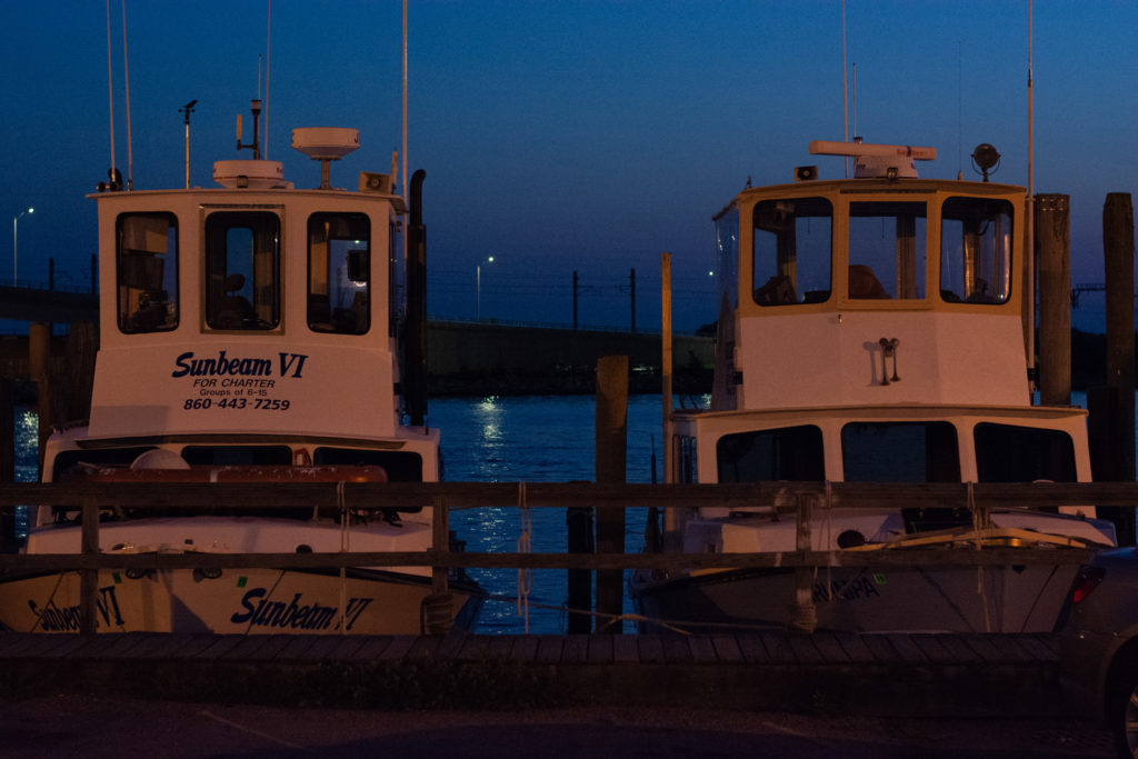 two boats sit next to each other at a dock in niantic, connecticut at dusk, photographed by jamie bannon photography.