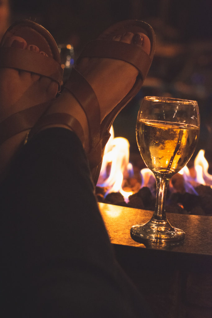 feet crossed with a glass of white wine by a fire pit in niantic, connecticut, photographed by jamie bannon photography.