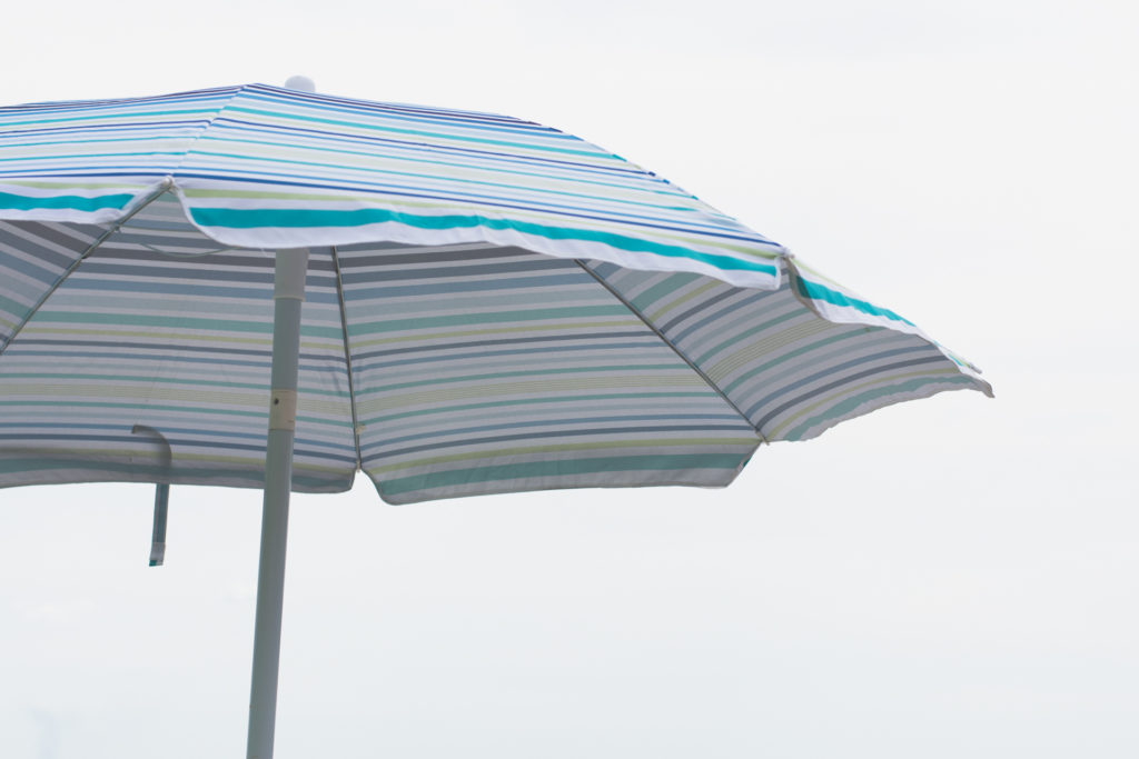 a blue striped umbrella sits against a white, overcast sky, photographed by jamie bannon photography
