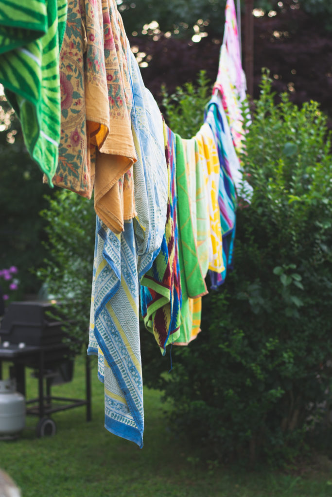 colorful beach towels hang on a clothes line in niantic, connecticut, photographed by jamie bannon photography.