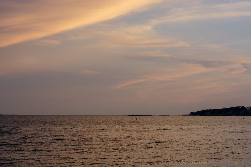 sunset over the water at the beach in niantic, connecticut, photographed by jamie bannon photography.