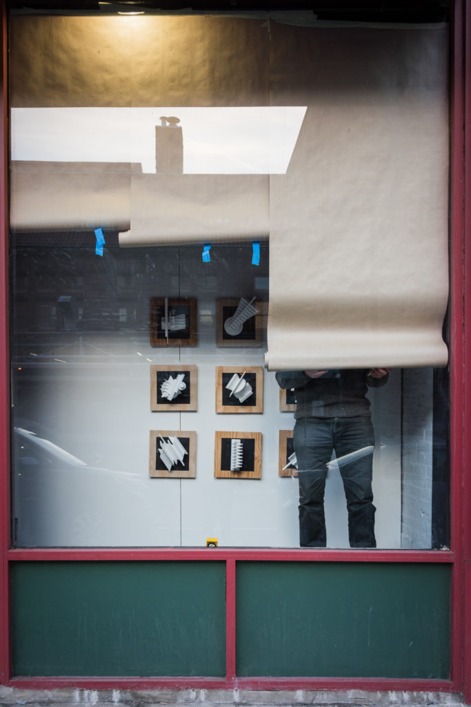 a gallery owner installs artwork in an empty storefront window in downtown hartford, connecticut, photographed by jamie bannon photography.