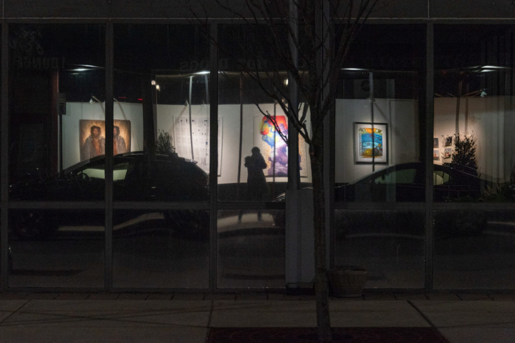 reflection of the photographer in front of an art exhibit in the storefront windows of downtown hartford, photographed by jamie bannon photography.